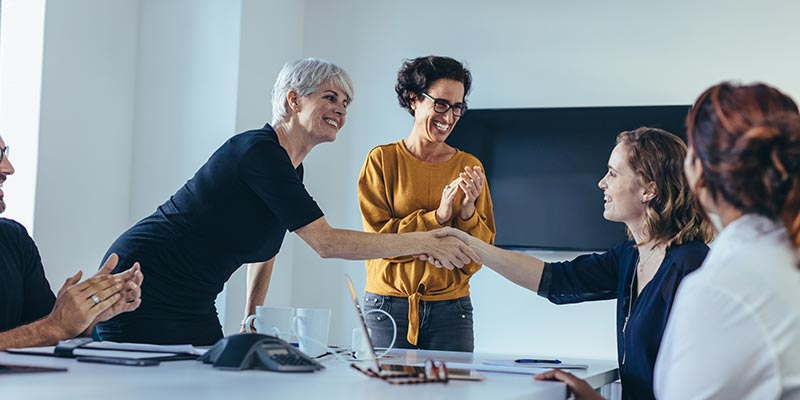 company leaders congratulating new manager on promotion