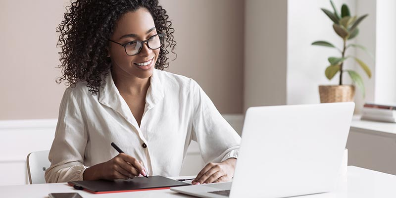 Young woman using a laptop at a desk to learn while taking notes