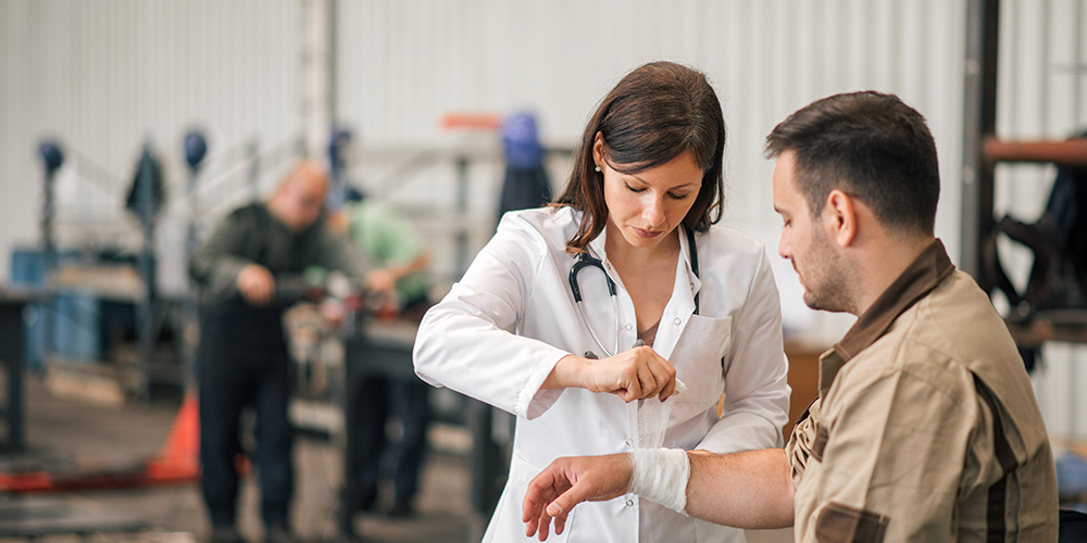 Medical professional assists worker after a crisis at a manufacturing plant.