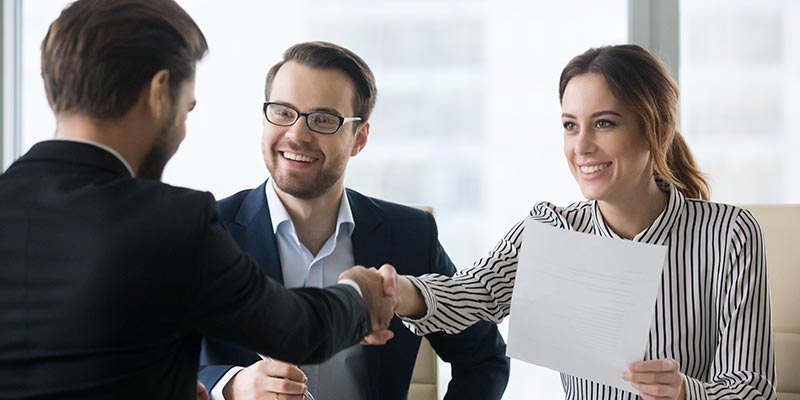 Human resources employees shaking the hand of a prospective new employee.