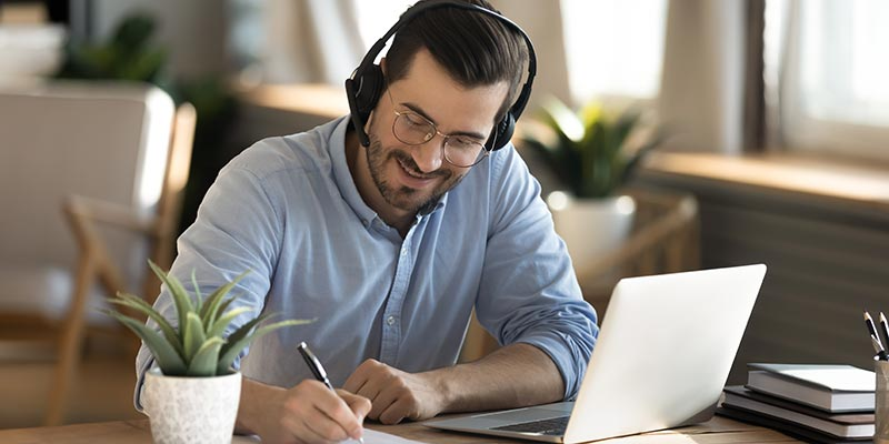 Male employee sitting at desk with headphones, learning on the computer and taking notes.