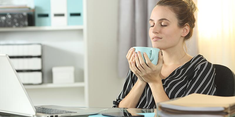 Businesswoman resting drinking coffee in her home office