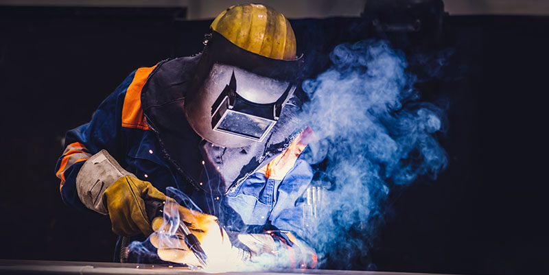 Blue-collar worker welds in a factory.