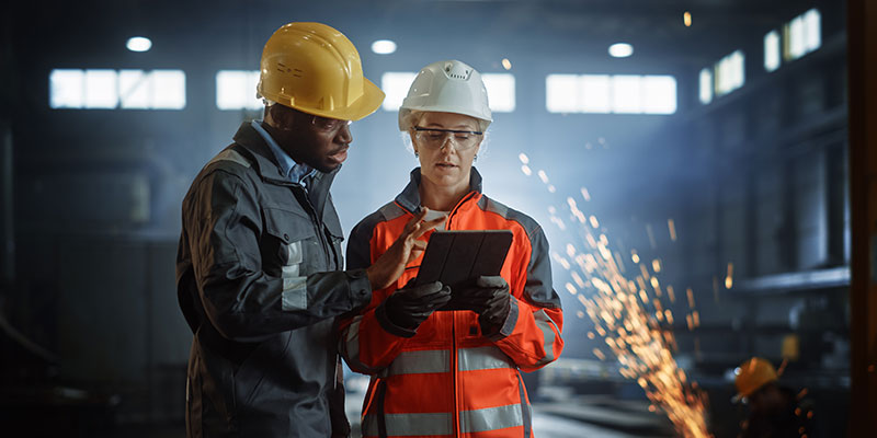 manufacturing managers using tablet and talking
