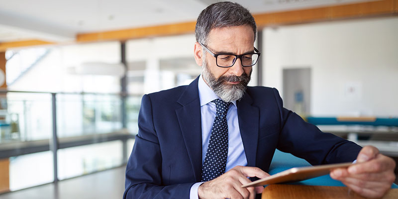 Executive completes training on a tablet computer while sitting at a table.